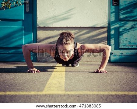 Photo of a toned young woman outside on the pavement doing pushups late in the day.