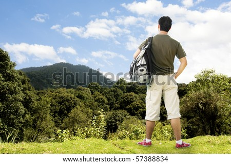 photo of a tourist atop beautiful mountain contemplating the view