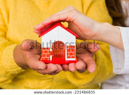 Photo of a toy house protected by hands - stock photo