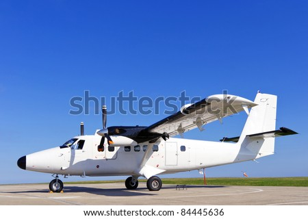 Photo of a twin propeller aircraft stationary on the runway on a bright sunny day with clear blue sky. - stock photo