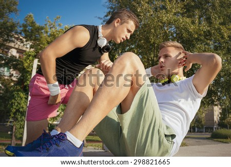 Photo of a two young man exercising doing sit ups outdoors - stock photo