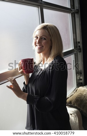 Photo of a very attractive blonde in a black shirt holding a red coffee cup and standing by a window. - stock photo
