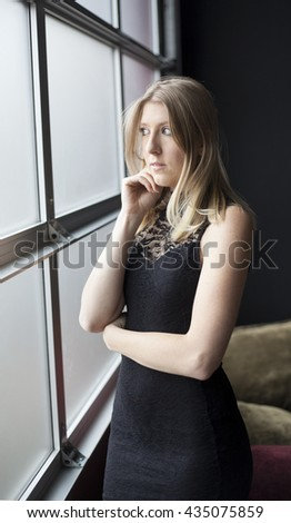 Photo of a very attractive blonde in a sexy black dress looking out a window at a party. - stock photo