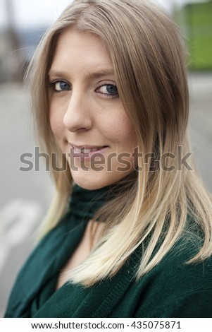 Photo of a very attractive blonde outside wearing a greet top. - stock photo