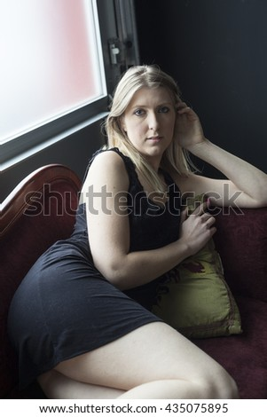 Photo of a very attractive blonde relaxing in a short black dress on a Victorian antique couch. - stock photo