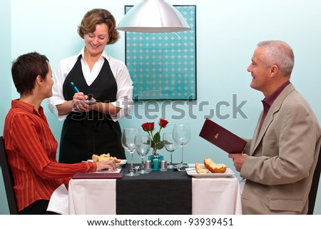 Photo of a waitress in a restaurant taking a food order from a mature couple who are sat at a table. - stock photo