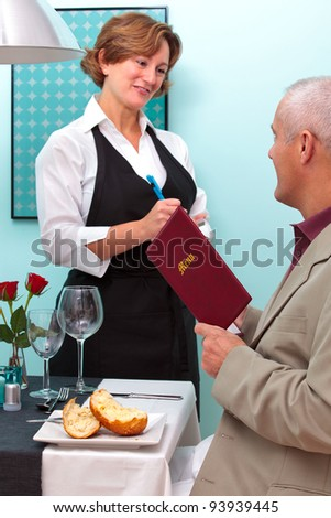 Photo of a waitress in a restaurant taking a food order from a mature male who is sat at a table holding a menu. - stock photo