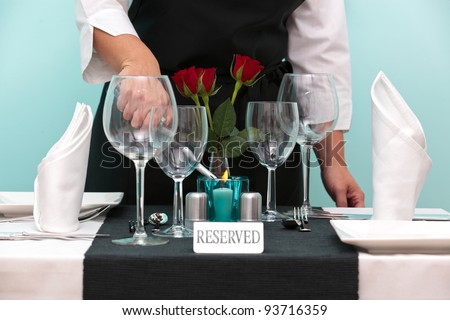 Photo of a waitress lighting a candle on a reserved table in a restaurant. - stock photo