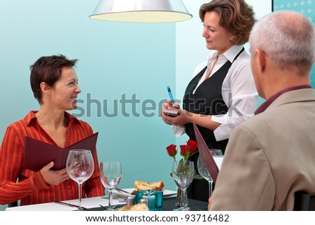 Photo of a waitress taking a food order from a mature couple dining in a restaurant - stock photo