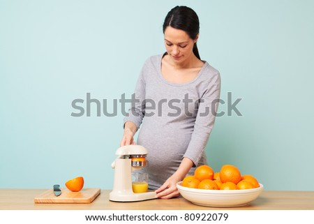 Photo of a 32 week pregnant woman in her kitchen preparing freshly squeezed orange juice. - stock photo