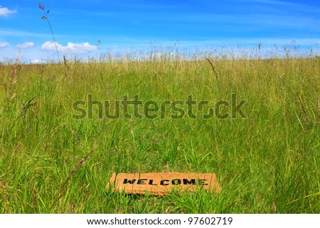 Photo of a welcome doormat in a grass meadow on a bright sunny day with blue sky and sunshine. - stock photo