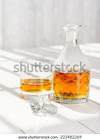 Photo of a whisky decanter and rocks glass on a table by a window. - stock photo