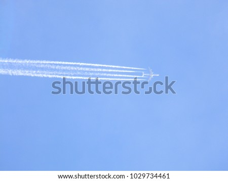 Photo of a white flying plane on a blue sky
