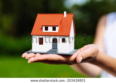 Photo of a white miniature house held by a woman - stock photo