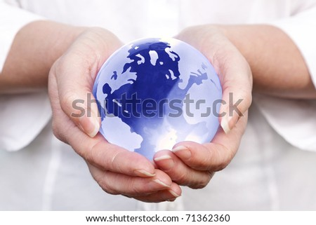 Photo of a woman holding a glass globe in her hands, concept image for worldwide and global related themes. - stock photo
