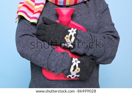 Photo of a woman holding a red hot water bottle to her chest whilst wearing hand kniitted woolen gloves trying to keep warm, good image for winter illness or warmth related themes. - stock photo