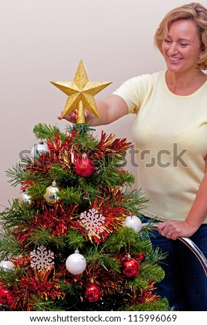 Photo of a woman standing on a ladder placing the star on top of her Christmas tree - stock photo