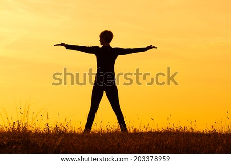 Photo of a woman with her arms outstretched looking at sunset,Greeting the sunset - stock photo