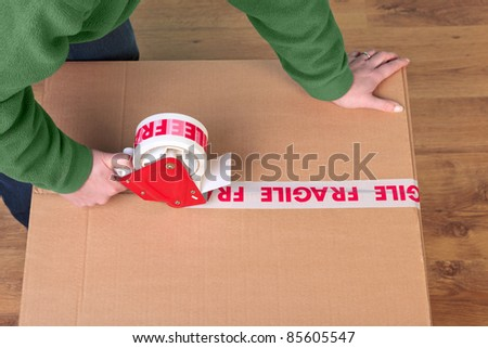 Photo of a womans hands taping up a cardboard box, can be used for removal or logistics related themes. - stock photo