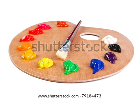 Photo of a wooden artists palette loaded with various colour paints and brush, isolated on a white background with clipping path. - stock photo