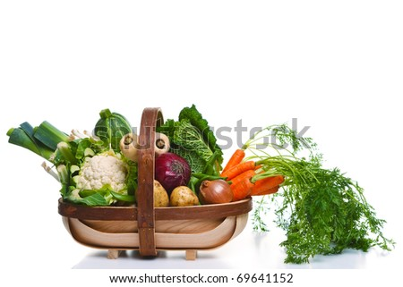 Photo of a wooden trug full of organic vegetables, isolated on a white background. - stock photo