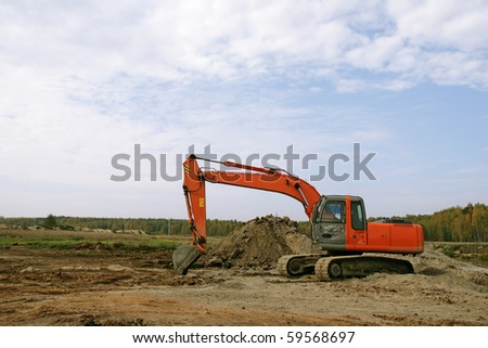 Photo of a working excavator in the countryside - stock photo
