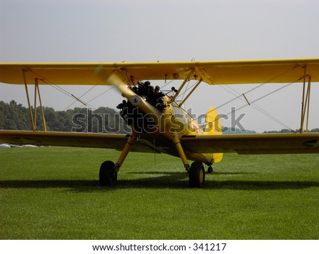 Photo of a yellow vintage 1940's Stearman PT-17 airplane landing, with propeller still spinning.