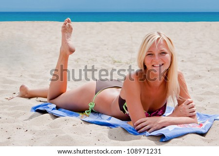 Photo of a young and beautiful woman resting on the sea coast - stock photo