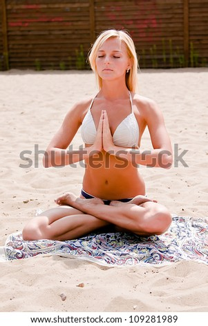 Photo of a young and beautiful woman who practices yoga on the beach - stock photo