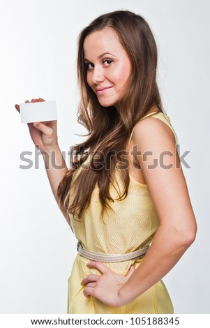 Photo of a young and beautiful woman with a business card in the hands of - stock photo