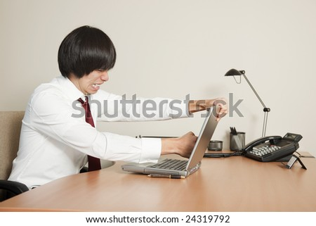Photo of a young Asian businessman punching his laptop computer screen. - stock photo