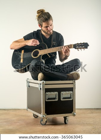 Photo of a young attractive man with long hair and beard sitting on a flight case and playing an acoustic guitar. - stock photo