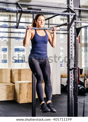 Photo of a young attractive woman doing pull-ups or chin-ups at a gym.