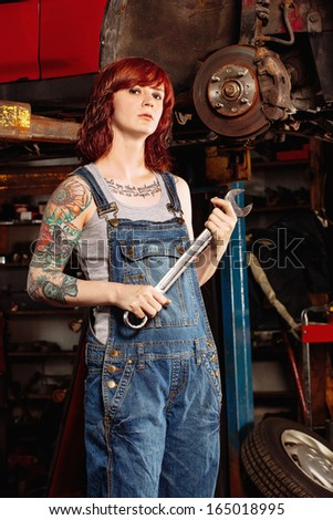 Photo of a young beautiful redhead mechanic wearing overalls and holding a huge wrench.  Attached property release is for arm tattoos.  - stock photo