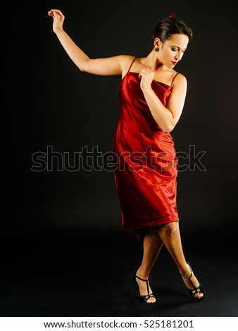 Photo of a young beautiful woman performing tango moves.