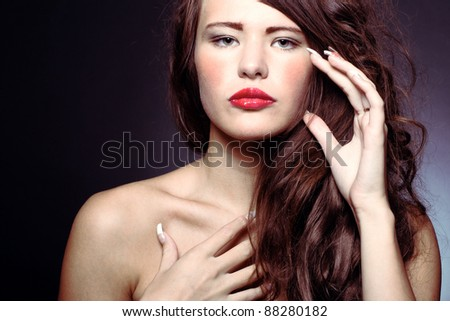 Photo of a young beautiful woman with bright makeup and manicure - stock photo