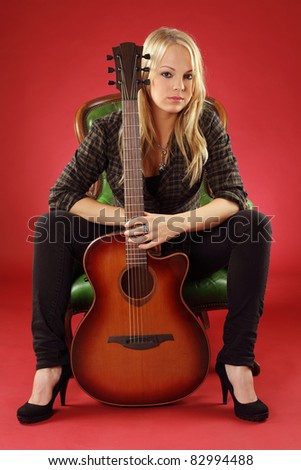 Photo of a young blond female holding a acoustic guitar.