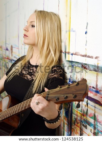 Photo of a young blond female holding an acoustic guitar and leaning up against a wall.