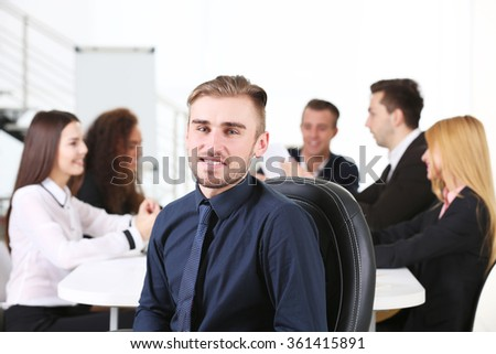 Photo of a young business man with his staff at the meeting in a conference room
