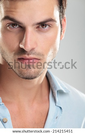 Photo of a young casual man in blue shirt, looking at the camera - stock photo