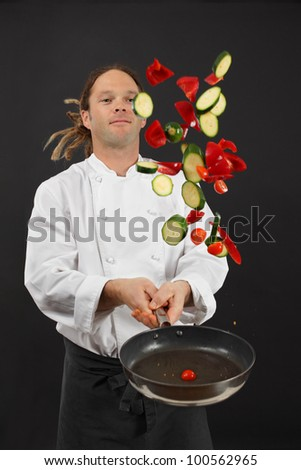 Photo of a young chef with dreadlocks tossing chopped vegetables in the air from a frying pan. - stock photo