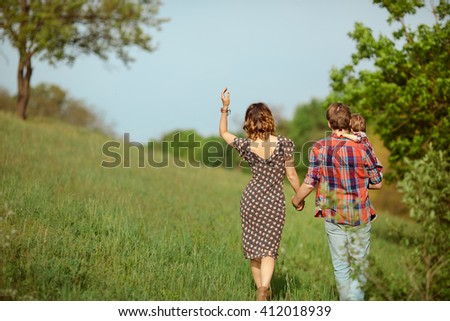 Photo of a young family enjoying a stroll in the park on a sunny summer day. - stock photo