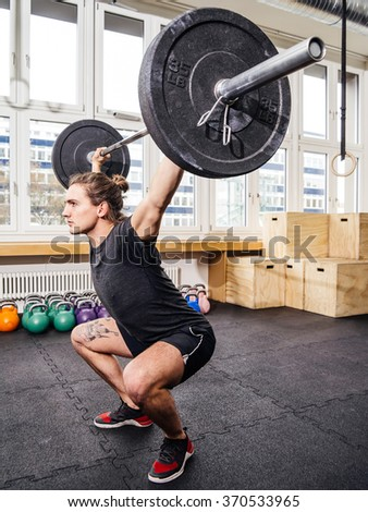Photo of a young man at a crossfit gym lifting a barbell. - stock photo
