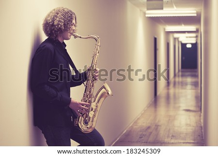 Photo of a young man playing the saxophone in a hallway. Heavily filtered.  - stock photo