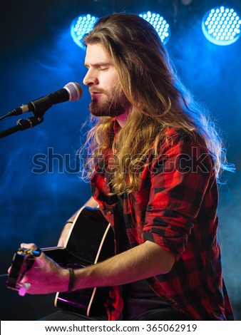 Photo of a young man with long hair and a beard singing and playing an acoustic guitar on stage with lights and concert atmosphere. - stock photo
