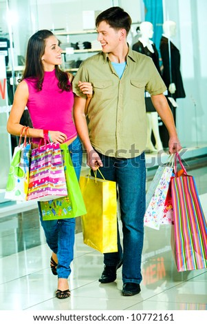 Photo of a young modern couple going shopping in the shopping mall carrying bags in their hands looking at each other