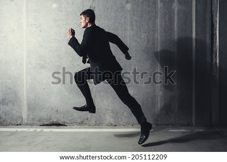 Photo of a young professional running against a concrete background - stock photo