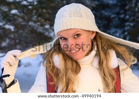 Photo of a young smiling girl in a knitted hat in winter. - stock photo