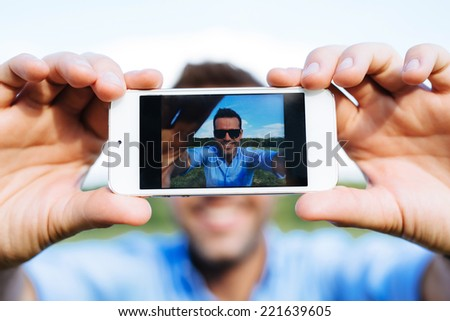 Photo of a young smiling man taking a selfie with his mobile - stock photo