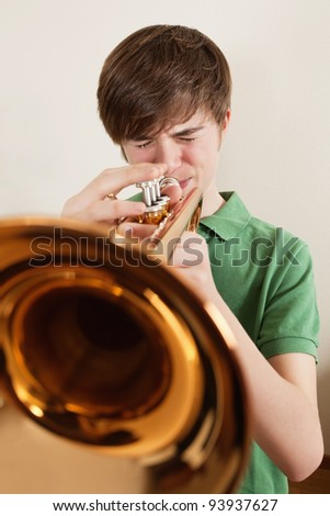 Photo of a young teen playing his gold trumpet. - stock photo